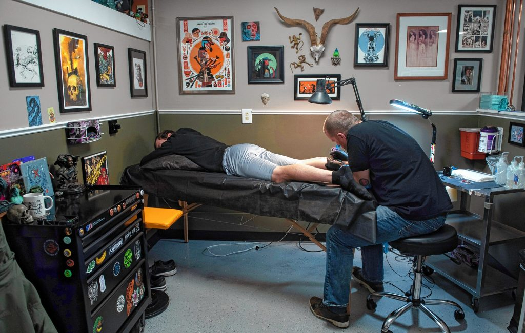 Eric Talbot works on a tattoo for Matt Miller at Oxbow Tattoo in Easthampton.