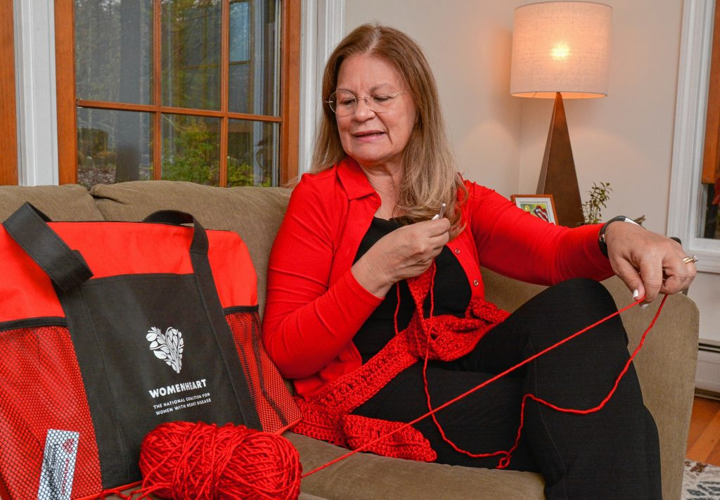 Lynette Bloise, who has become a WomenHeart champion, crochets a scarf at her home in Pelham.