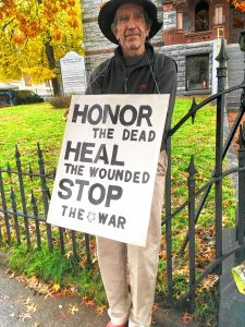 "Andrew Larkin with his sign. It reads ""Honor the dead / Heal the wounded / Stop the war."""