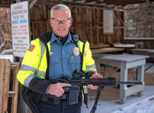 Ken Ouimette, with the Conway police department, poses with a AR15 Patrol Riffle at the Conway Sportsman Club.