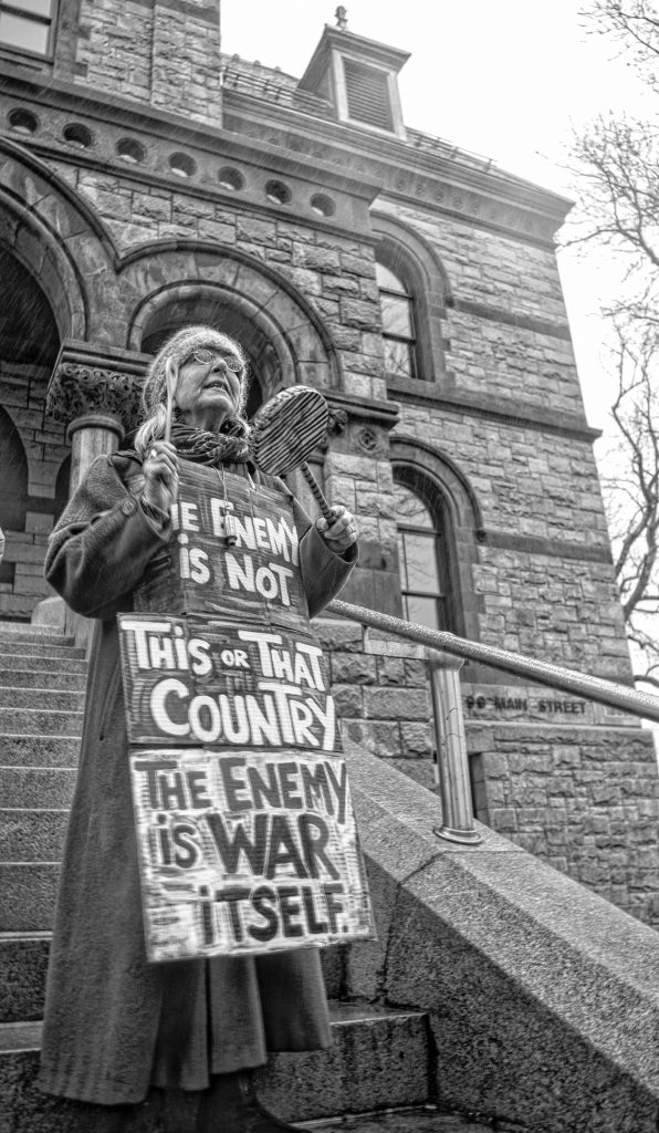 Claudia Lefko, one of the founders of the regular Saturday morning antiwar protest, with her sign on the steps of the courthouse.