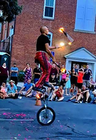 Matica Circus fire juggling on a unicycle.