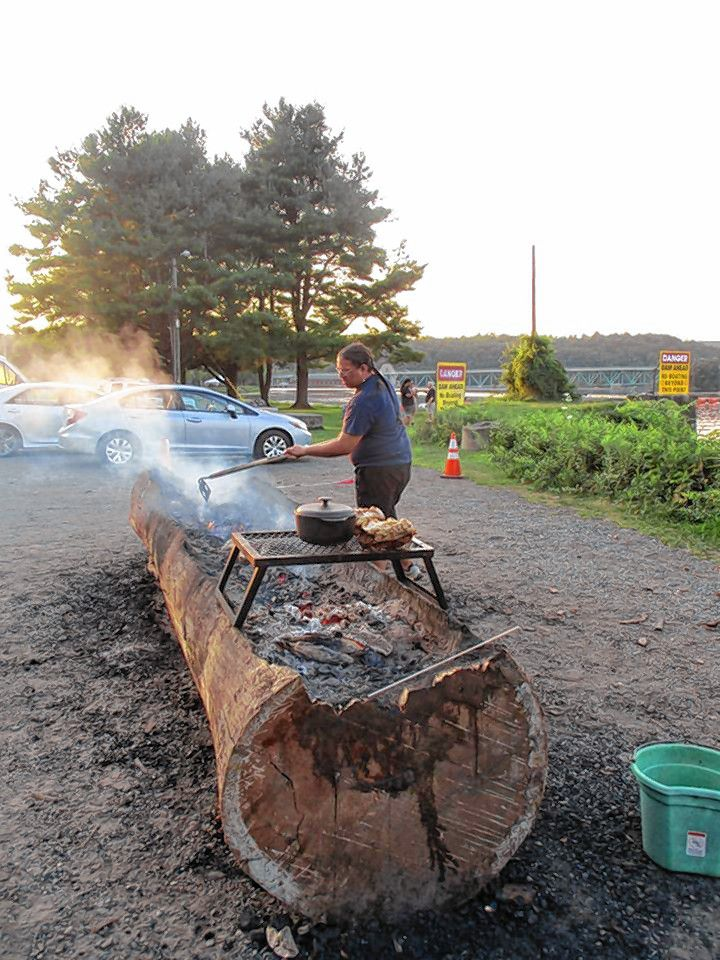 Jonathan Perry, of the Aquinnah Wampanoag, rakes coals last summer at Turners Falls from a log he's hollowing out to make a mishoon, a traditional dugout canoe. A group of these boats will be launched in the Connecticut River this summer as part of River Stories 2020.
