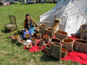 "Jennifer Lee at a past Pocumtuck Homelands Festival in Turners Falls with some of the baskets she makes. ""A lot of native culture has been lost, but a lot has survived,"" she says."