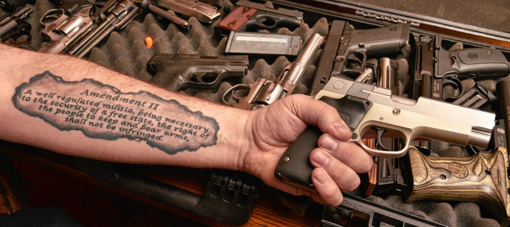 Kirk Whatley displays a box of handguns he uses for his NRA Certified Basic Pistol class at his home in Hadley, Tuesday, Dec. 17, 2019. His forearm bears a tattoo of the Second Amendment to the Constitution.