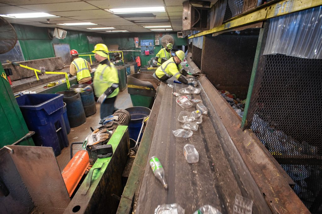 Workers separate different materials in the sorting room of the Springfield Materials Recycling Facility on Tuesday, Feb. 4, 2020.