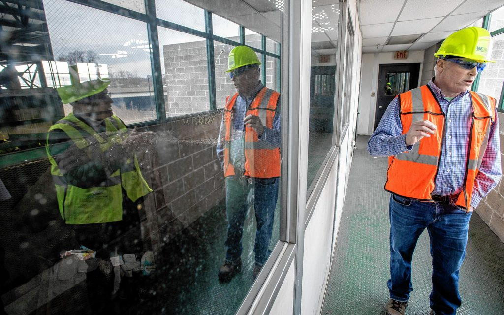 Springfield Materials Recycling Facility Plant Manager Michael Moores, right, is joined by SMRF Advisory Board Vice Chair Arlene Miller, reflected at left, on the observation deck of the operation on Tuesday, Feb. 4, 2020.
