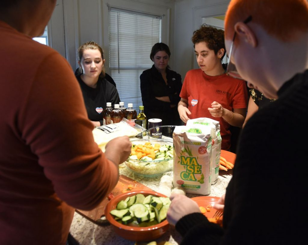 Rafaella Fabrizi, Joelle Bueno, and Emma Kinney, watch as Natty demonstrates how to make pupusas as a collaboration between the Trans Asylum Seeker Support Network and a University of Massachusetts anthropology class.