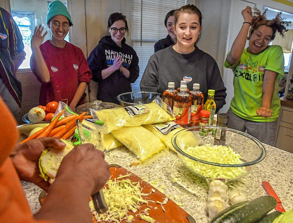 Jax Padilla, Rafaella Fabrizi, and Zulay Holland watch along with others in a pupusa-making event, a collaboration between the Trans Asylum Seeker Support Network and a UMass Amherst anthropology class taught by Meredith Degyansky and Boone Shear. Natty demonstrates how to make pupusas.