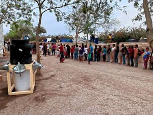 Asylum seekers lined up for food with a handwashing station nearby.