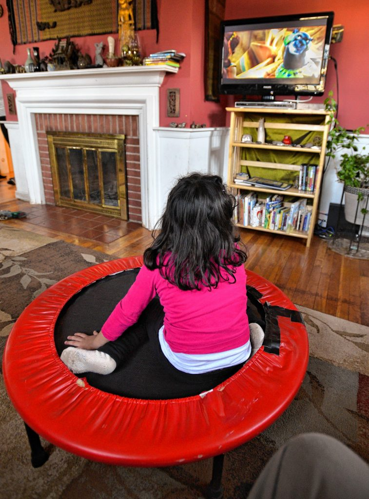 A 3-year-old girl who has been given asylum along with her mother watches TV at the home of Lynne, Thursday, Jan. 30.
