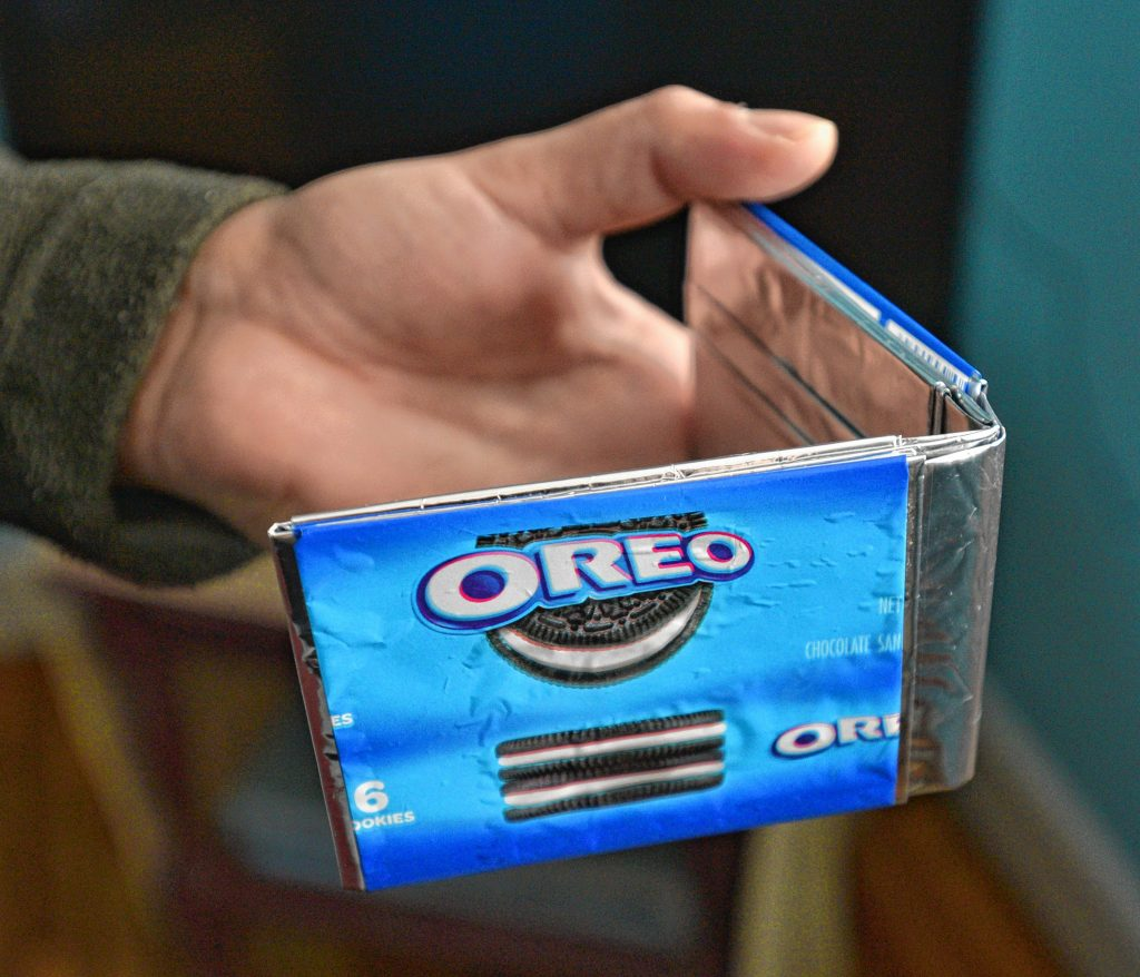 A man seeking asylum holds a wallet he made from Oreo wrappers while in detention, at his apartment, Tuesday, Feb. 11, 2020.