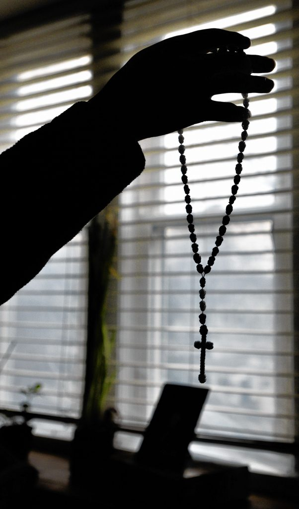 A man seeking asylum holds a crucifix at his apartment, Tuesday, Feb. 11, 2020, that a friend gave him while they were in detention together.