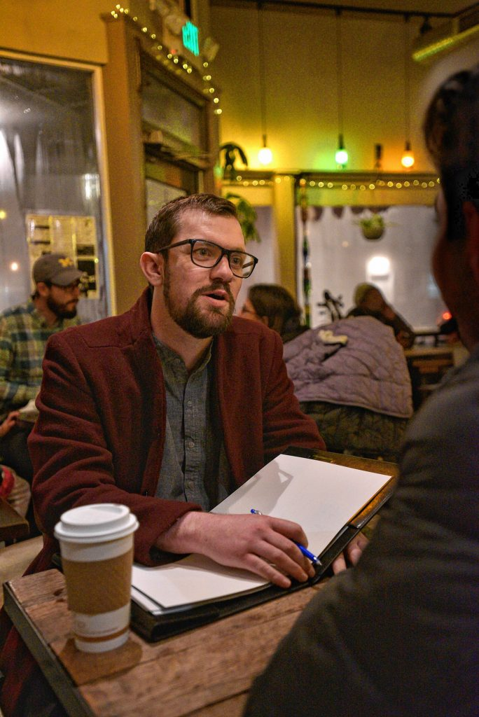 Jonathan Jenner, who is a volunteer for Western Massachusetts Asylum Support Network, talks with a client, Thursday, Feb. 13, 2020, at The Roost in Northampton.