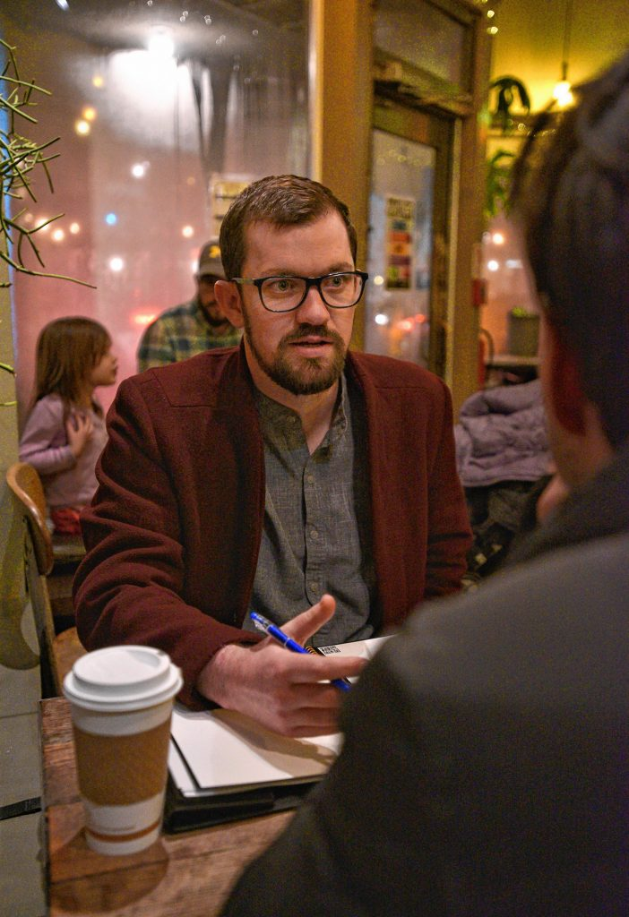 Jonathan Jenner, who is a volunteer for Western Massachusetts Asylum Support Network, talks with a client at The Roost in Northampton.