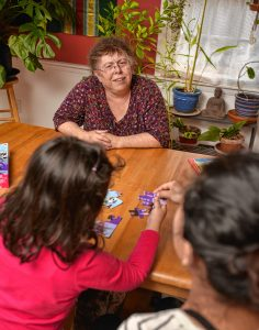 Lynne, top, talks to a woman and her 3-year-old daughter who she has given asylum to in her home, Thursday Jan. 30 as they put a puzzle together.