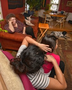Lynne, top, relaxes in her living room beside a woman and her 3-year-old daughter she has given asylum to, Thursday, Jan. 30.