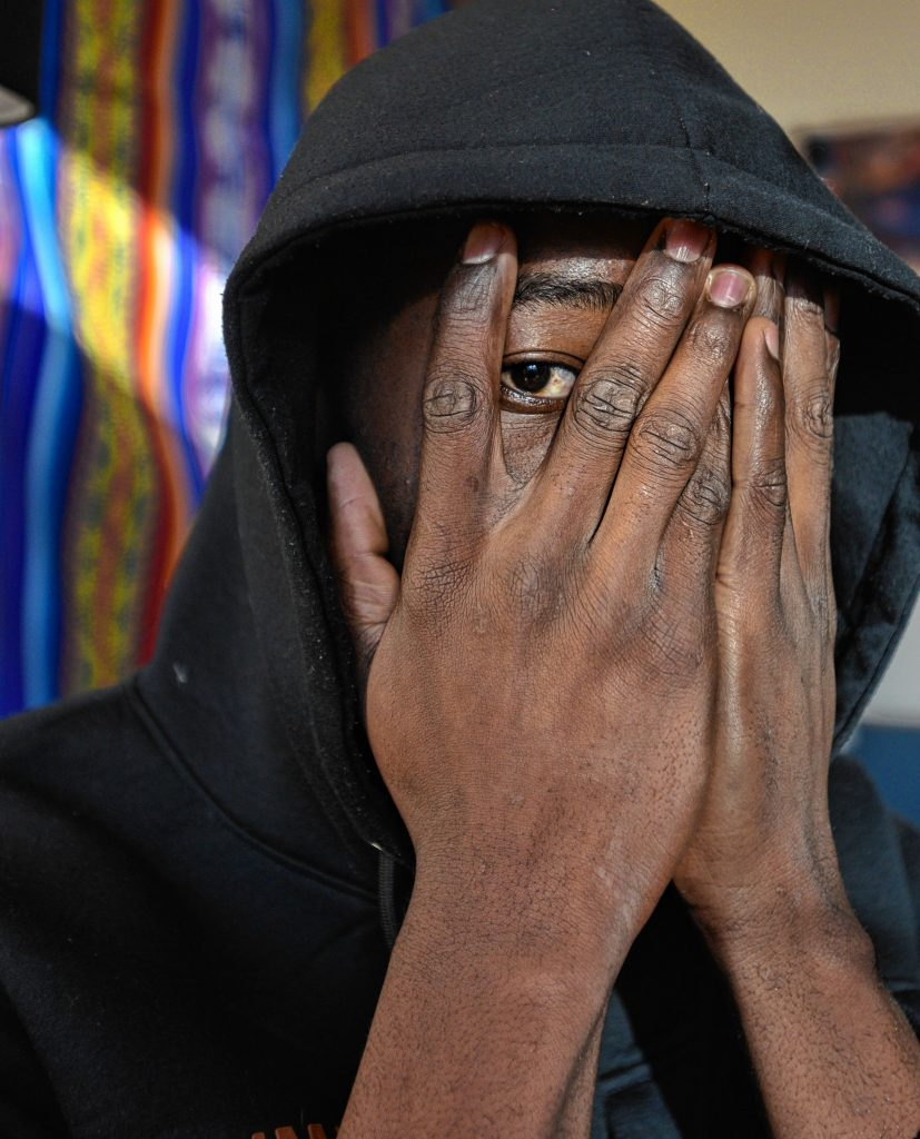 A man from west Africa who has received asylum status covers his face to hide his identity, Monday, Feb. 3, 2020.