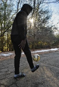 A man from west Africa who has received asylum status dribbles a soccer ball, Monday, Feb. 3, 2020.