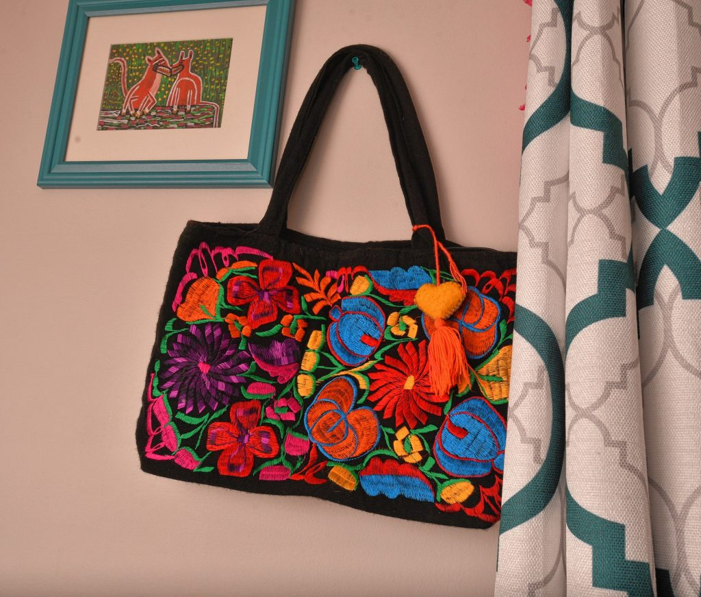 An embroidered handbag given to Natty is hung on a wall in her room at the home of her sponsor, Friday Mar. 6, 2020.