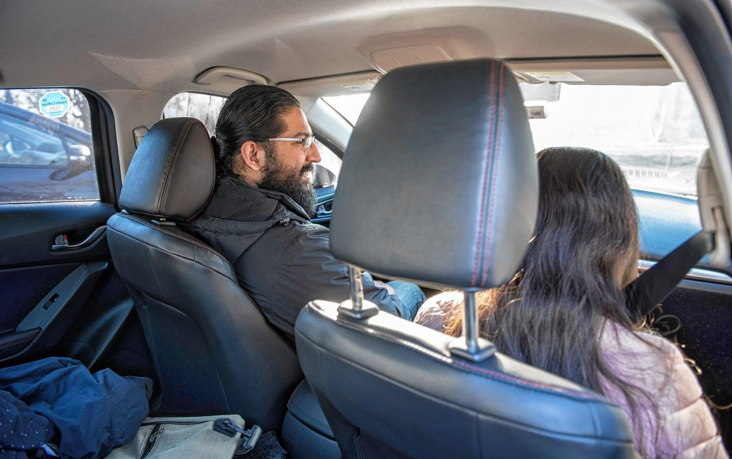 Western Massachusetts Asylum Support Network volunteer Osman Keshawarz, left, gives a ride to a woman, in the process of seeking asylum, from Hadley to the Immigration and Customs Enforcement office in Hartford on Wednesday morning, Jan. 29, 2020.
