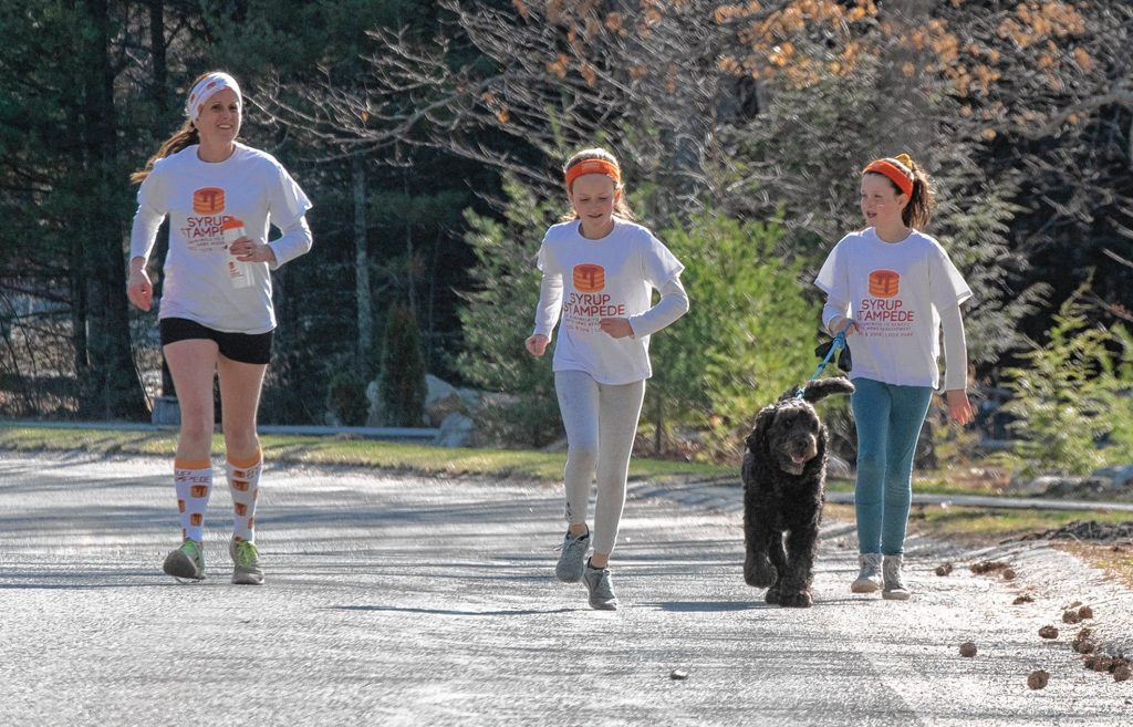 "Carol McMurrich with daughters Fiona Reynolds, 10, and Maeve Reynolds, 8, and dog Teddy. Though the Empty Arms fundraiser was rescheduled to Nov. 14, they still run ""to keep spirit alive,"" said McMurrich."