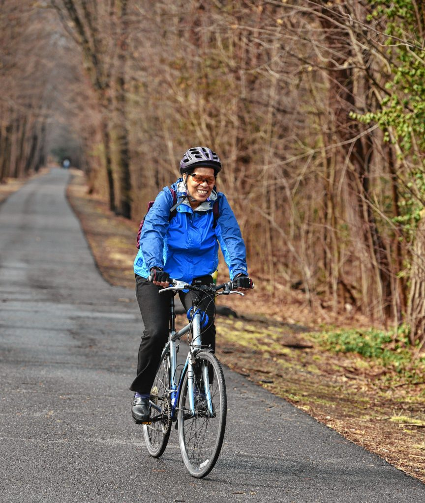 Andrea Hairston rides on the Northampton Rail Trail in Florence in mid March. She uses the path to commute to her job teaching writing at Smith College.