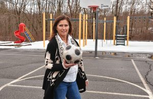 Jean Fay, who is a special education paraeducator at Crocker Farm School in Amherst, stands on the school's empty playground, Tuesday, Mar. 24, 2020. She said her students liked to play soccer there.