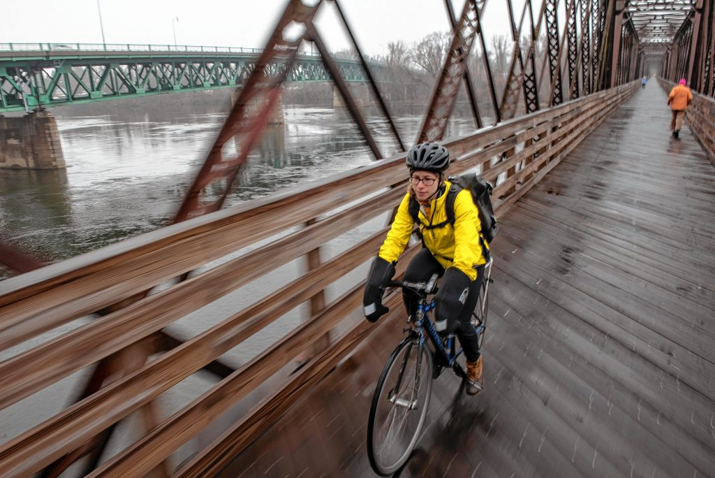 Physical therapist Jess Goldberg of Florence has regularly commuted by bicycle to her job in Hadley, a roughly 30-minute trip. Here she's seen crossing the Connecticut River on the Norwottuck Rail Trail on her way to Tran's World Food Market in Hadley.