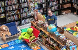 "Luis Soria, principal of Dr. Marcella R. Kelly School in Holyoke, stands in the school's normally bustling library on Wednesday, March 25, 2020. When the morning bell rang during the photo session, Soria remarked, ""A bell for no-one."""
