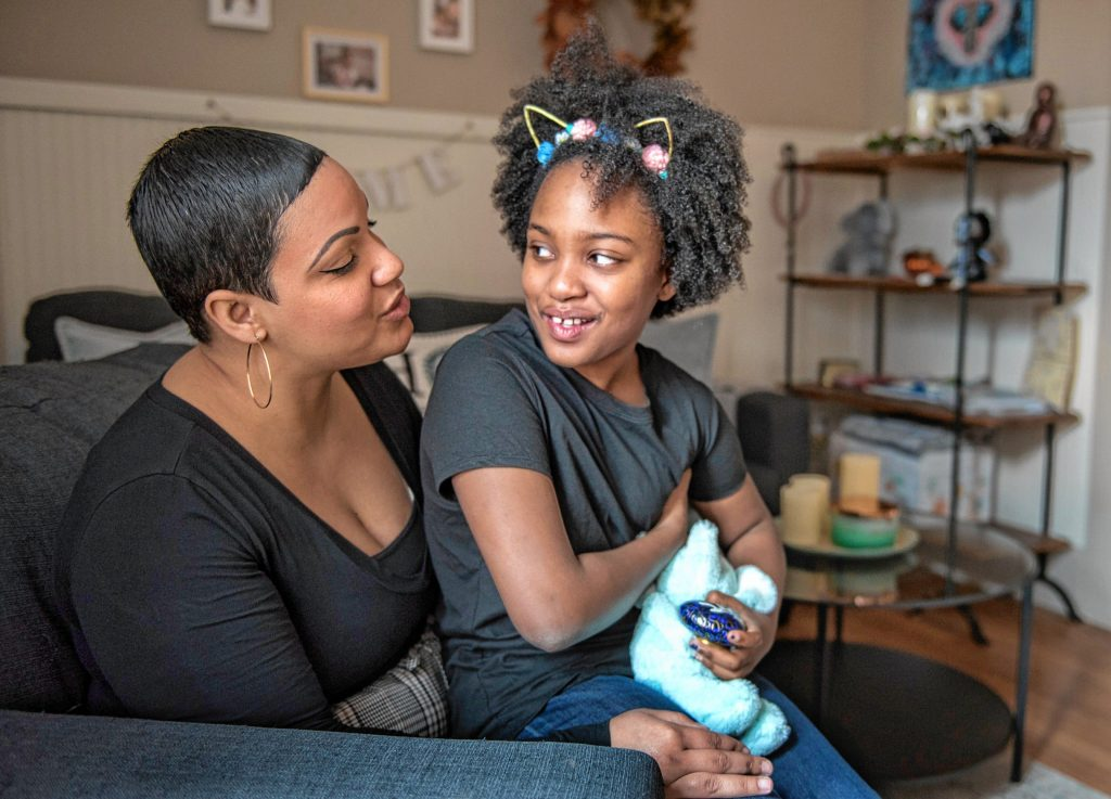 Emily Collins and her daughter, Gabrielle Collins-Hill, 8, pose in their Holyoke home with an urn containing the ashes of her son, Sebastian, who died in 2018 at the age of 2 weeks.