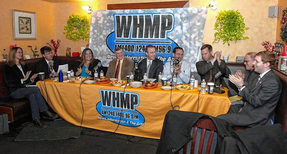 Holyoke Mayor Alex Morse, far right, and Northampton Mayor David Narkewicz, third from right, are shown in a framed photo, taken by longtime Gazette photographer (now retired) Gordie Daniels,  in WHMP's studio. The photo shows the two mayors, along with all the area's other chief executives at a radio summit at Sylvester's Restaurant. All are gone now.