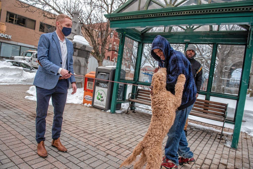 Holyoke Mayor Alex Morse greets residents Abram Marshall, foreground, and Antwon Davis at the bus stop outside city hall while walking his dog, Oliver, a six-month-old labradoodle, on Thursday, Feb. 4, 2021.