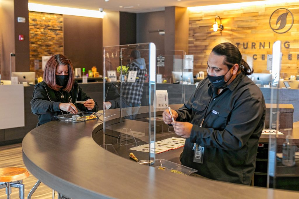 Steven Robles, team leader at Turning Leaf Centers dispensary in Northampton, shows Marketing Coordinator Nicole Desjardins how to handroll a joint.